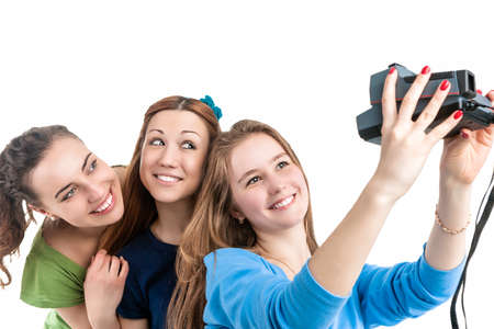 photocamera: Lifestyle Concept and Ideas. Three Young Positive Smilig Caucasian Ladies Making Self Photographs With Photocamera. Isolated Over White Background. Horizontal Image Orientation Stock Photo