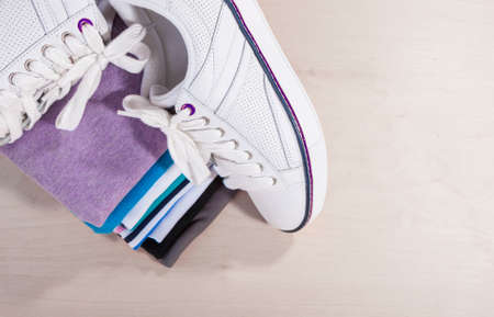 plimsoll: Fashion Ideas and Concepts. Pair of White Fasionable Sneakers Close to Stack of Prepared Clothing. Horizontal Image with Copy Space Stock Photo
