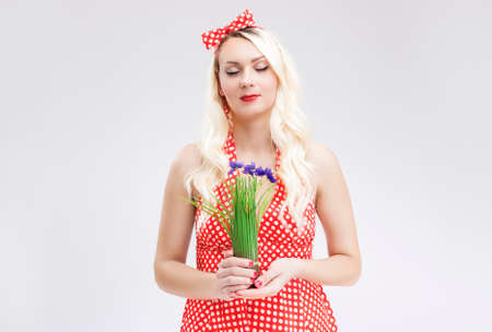 charm temptation: Sensual Caucasian Blond Female in Red Polka Dotted Dress Dreaming. Holding Bunch of Lilac  Flowers in Hands in Front. Horizontal Image Composition Stock Photo