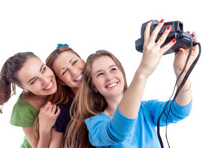 photocamera: Youth Lifestyle Concept and Ideas. Three Young Positive Smilig Caucasian Ladies Making Self Photographs With Photocamera. Isolated Over White Background. Horizontal Image Orientation