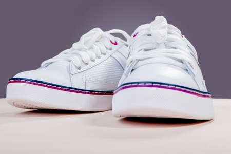 plimsoll: Pair of White Fashionable Leather Trainers on Wooden Surface Against Gray Background. Horizontal Image Orientation