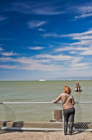 vertical image: Caucasian Woman Contempalting Sea In San-Francisco Bay Standing Near Fence. Vertical  Image Stock Photo