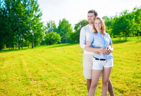 intimacy: Intimacy and Relationships Concept and Ideas. Young Caucasian Couple Standing Together Embraced. Hands Folded in Front. Horizontal  Image Composition Stock Photo