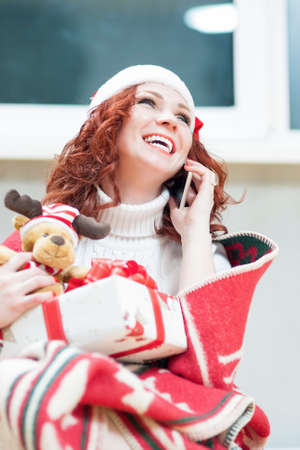 redhaired: Positively Looking Expressive Red-Haired Caucasian Santa Helper Girl with Christmas Gift Box. Speaking by Cellphone and Laughing  Indoors. Vertical Orientation