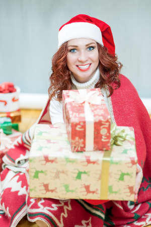 red haired: Christmas and New Year Concept and Ideas. Happy Looking Young Caucasian Red Haired Female in Santa Hat Posing with Christmas Gifts