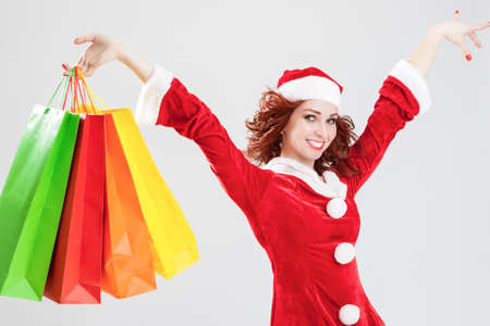 exclaiming: Exclaiming and Happy Caucasian Santa Girl With Many Colorful Shopping Bags. Posing Against White Background. Horizontal Image Composition