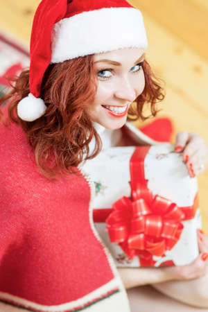 santa girl: Christmas and New Year Ideas and Concepts. Smiling Caucasian Red-Haired Santa Girl Holding Present Box and Looking Upwards. Vertical Image Composition Stock Photo