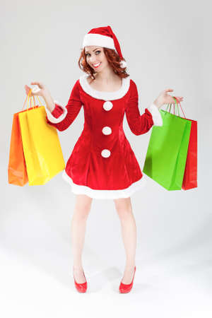 two minds: Happy Smiling Caucasian Santa Girl in Two Minds With Plenty of Colorful Shopping Bags. Posing Against White Background. Vertical Image