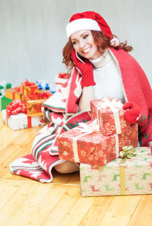 santa girl: Pretty and Laughing Red-Haired Cucasian Santa Girl With a Bunch of Gift Boxes Speaking by Cellphone Indoors. Sitting Under the Plaid on Floor. Vertical Image Orientation Stock Photo