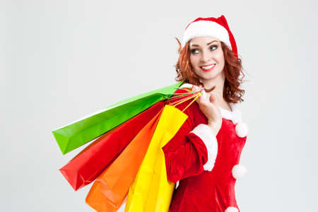 santa girl: New Year and Christmas Concept and Ideas. Smiling Caucasian Red-Haired Santa Girl with Shopping Bags. Against White Background. Horizontal Image Composition