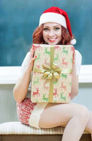 'snow maiden': Christmas, New Year, X-Mas Concepts and Celebrations. Young Caucasian Santa Helper Girl With Big Present Box. Posing as Snow Maiden in Santa Hat.Vertical Image Orientation