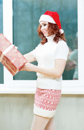 santa girl: Caucasian Santa Girl Holding Christmas Box Gift. Portrait of Happy Woman Posing in Santa Hat With Multiple Presents Offering to Client Indoors. Vertical Image