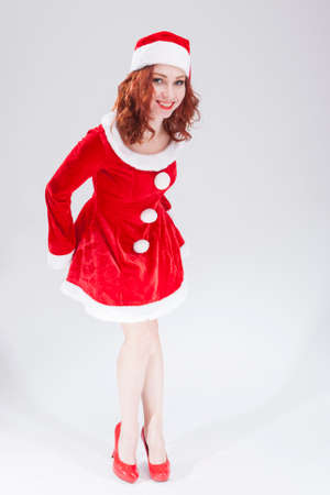 red haired: New Year Concept and Ideas. Happy Looking Young Caucasian Red Haired Female in Santa Hat Stock Photo