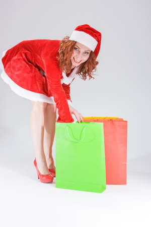 red haired: Christmas and New Year Concept and Ideas. Happy Looking Young Caucasian Red Haired Female in Santa Hat Posing With Shopping Bags