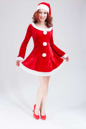 red haired: Christmas and New Year Concept and Ideas. Happy Looking Young Caucasian Red Haired Female in Santa Hat