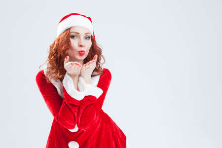 red haired: Christmas and New Year Concept and Ideas. Happy Looking Young Caucasian Red Haired Female in Santa Hat Posing With Air Kissing Stock Photo