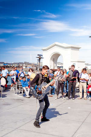exclaim: San-Francisco-United States, July 13, 2014: Positive Caucasian Male Multiplayer Musician Performing Outdoors on San-Francisco Pier on July 13, 2014 in San-Francisco, California, United States of America Editorial