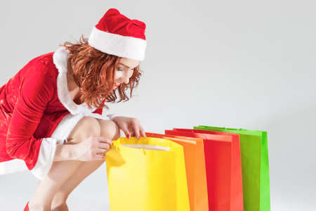 santa helper: Happy Smiling Caucasian Ginger Santa Helper Girl with Colorful Shopping Bags. Posing Against White Background. Horizontal Image Orientation Stock Photo