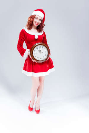 gleeful: Christmas Time Concept. Full length Portrait of Smiling Gleeful Sexy Red Haired Santa Helper Posing with Big Round Clock. Standing Against White Background. Vertical Image Orientation
