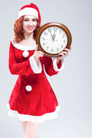 gleeful: Time and Christmas Holiday Concept. Smiling and Gleeful Red-Haired Santa Helper Showing Time on Big Clock. Posing Against White Background. Vertical Image Composition