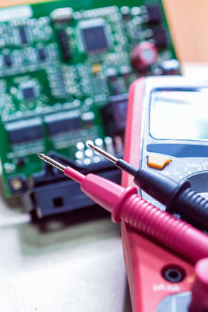electrolytic: Measurement Pins Of Digital Multimeter Tester Against of Pinted Circuit Boards With Mounted Components on The Background. Vertical Image Composition Stock Photo