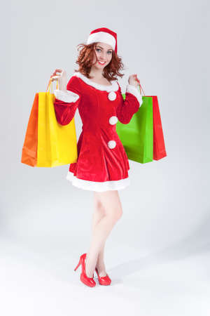 santa helper: Full Length Portrait of Smiling Sexy Caucasian Ginger Santa Helper Girl with Plenty of Colorful Shopping Bags. Posing Against White. Vertical Image Composition