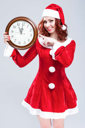 gleeful: Time and Christmas Holiday Concept and Ideas. Gleeful Red-Haired Santa Helper With Big Round Clock and Showing Time. Posing Against White Background. Vertical Image Orientation Stock Photo