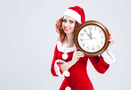gleeful: Time and Christmas Holiday Concept. Smiling and Gleeful Red-Haired Santa Helper Showing Time on Big Clock. Posing Against White Background. Horizontal Image Composition