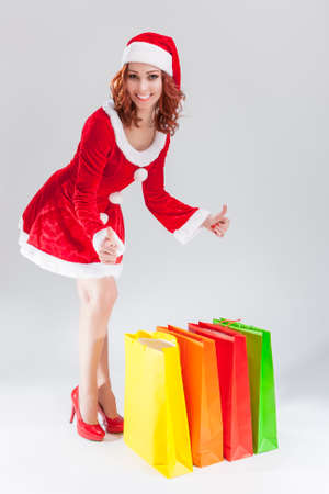 santa helper: Portrait of Young Smiling Caucasian Ginger Santa Helper Girl with Colorful Shopping Bags.Showing Thumbs up Sign. Posing Against White Background. Vertical  Composition
