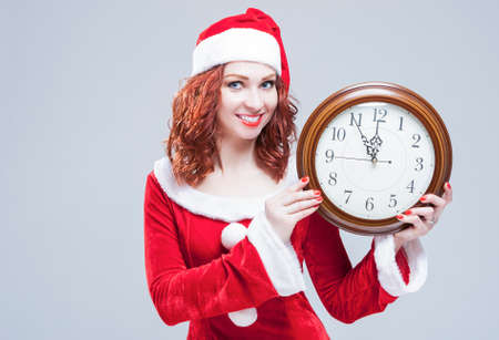 gleeful: Time and Christmas Holiday Concept. Portrait of Smiling and Gleeful Red-Haired Santa Helper Showing Time on Big Clock. Against White Background. Horizontal Shot