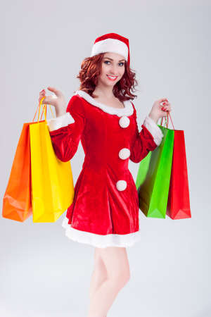 santa helper: Sexy Caucasian Ginger Santa Helper Girl with Plenty of Colorful Shopping Bags. Posing Against White Background. Vertical Image Orientation