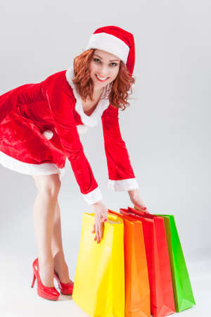 santa helper: Happy Smiling Caucasian Ginger Santa Helper Girl with Colorful Shopping Bags. Posing Against White Background. Vertical Image Orientation Stock Photo