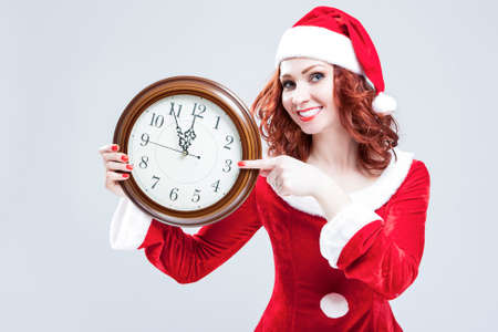gleeful: Time Concept and Ideas. Gleeful Red-Haired Santa Helper With Big Round Clock and Showing Time. Posing Against White Background. Horizontal Image Composition Stock Photo