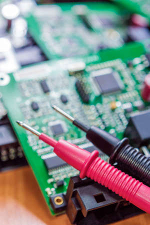 circuitry: Laboratory Components and Staff. Pins of Digital Multimeter In Front of Printed Circuit  Boards with Integrated Circuitry. Vertical Image Stock Photo