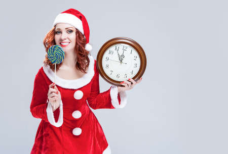 gleeful: Christmas Holiday Concept and Ideas. Portrait of Gleeful Red-Haired Santa Helper With Iced Lolly and Big Round Clock. Posing Against White Background. Horizontal Image Orientation