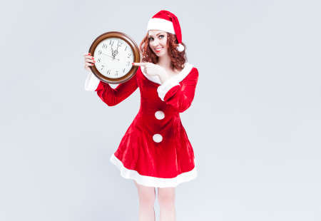 gleeful: Time and Christmas Holiday Concept and Ideas. Gleeful Red-Haired Santa Helper With Big Round Clock and Showing Time. Posing Against White Background. Horizontal Shot