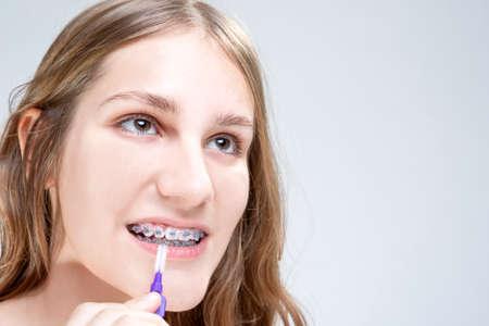 fix jaw: Dental Hygiene Concepts. Caucasian Teenage Girl Using Bristle Teeth Brush for Brackets. Horizontal Image Orientation Stock Photo