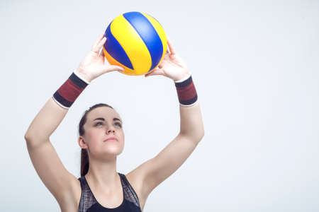 female volleyball: Sport Concepts and Ideas. Professional Female Volleyball Athlete Serves the Ball. Against White Background. Horizontal Image