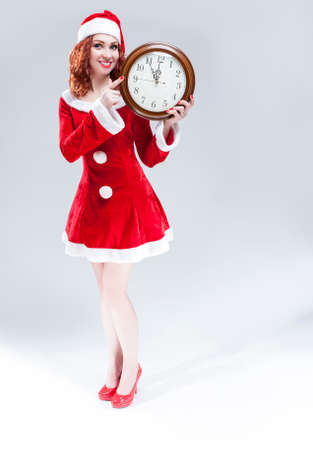 gleeful: Time and Christmas Holiday Concept. Full Length Portrait of Smiling and Gleeful Red-Haired Santa Helper Showing Time on Big Clock. Against White Background. Vertical Shot