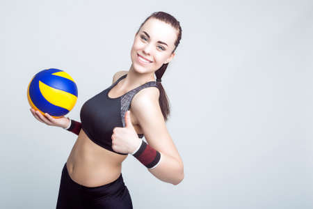female volleyball: Sport Concepts and Ideas. Professional Female Volleyball Athlete With Ball Showing Thumbs Up Sign. Against White Background. Horizontal Image