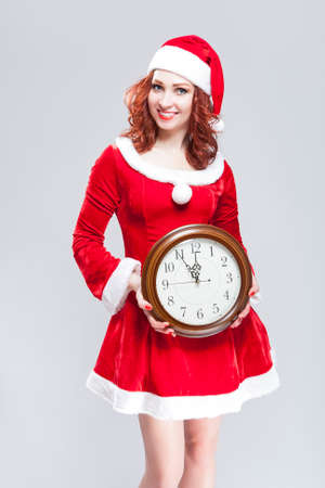 gleeful: Christmas Time Concept. Smiling Gleeful Sexy Red Haired Santa Helper Posing with Big Round Clock. Standing Against White Background. Vertical Shot
