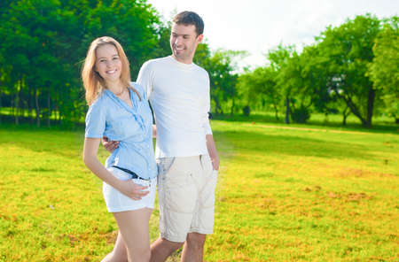 25 30 years: Family Concept. Young Caucasian Family  Together Outdoors Having a Walk in Park. Nature Background. Horizontal Shot Stock Photo