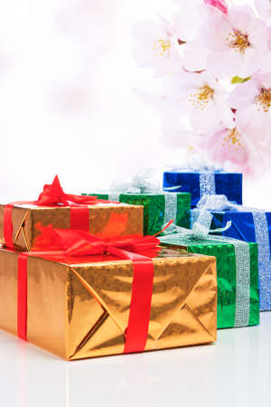 Presents and Celebration Concepts. Many Colorful Wrapped Up Gift Boxes Standing In Line Together. Against Flowery Abstract Background. Vertical Image Stock Photo