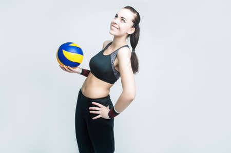 female volleyball: Sport Concepts and Ideas. Professional Female Volleyball Athlete With Ball. Against White. Horizontal Composition