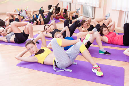 stratching: Sport, Fitness and Pilates Concepts. Group of Seven Caucasian Female Athletes Stratching Legs Muscles on Sport Mats. Horizontal Image