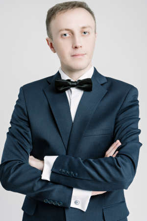against white: Portrait of Caucasian Handsome Man in Blue Suite Against White Background. Vertical Shot Stock Photo