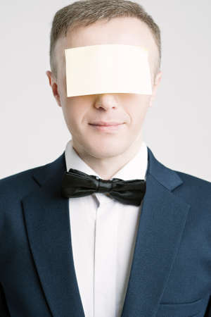 against white: Business People Concepts And Ideas. Portrait of Caucasian Businessman With Paper Sticker on Forehead. Against White. Vertical Image Stock Photo