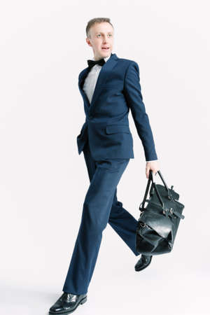 against white: Business People Concepts. Young Caucasian Handsome Man With Bag Striding Against White. Vertical Image Orientation Stock Photo