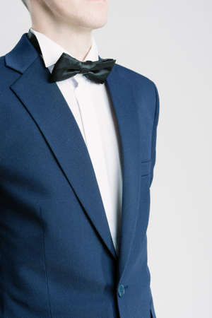 man in suite: Closeup Portrait of Young Caucasian Man in Blue Suite and Bow Tie. Vertical Shot Stock Photo