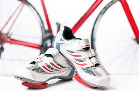cleats: Cycling and sport Concept. Sport Cycling Shoes with Cleats and Covers On Against Red Professional Road Bike. Horizontal Image